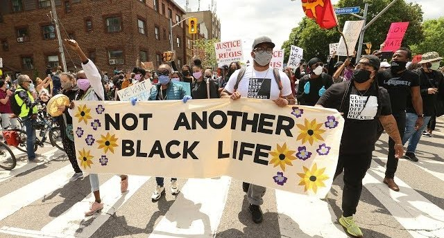 """Protester march peacefully in Toronto with sign """"Not Another Black Life"""""""
