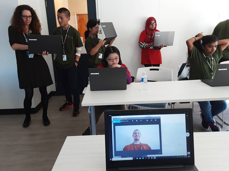 Six Project SEARCH students are with their teacher in a classroom
